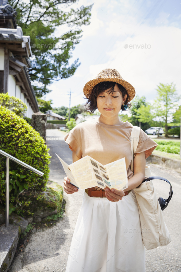 Japanese woman wearing hat and holding map standing outside Buddhist temple. - Stock Photo - Images