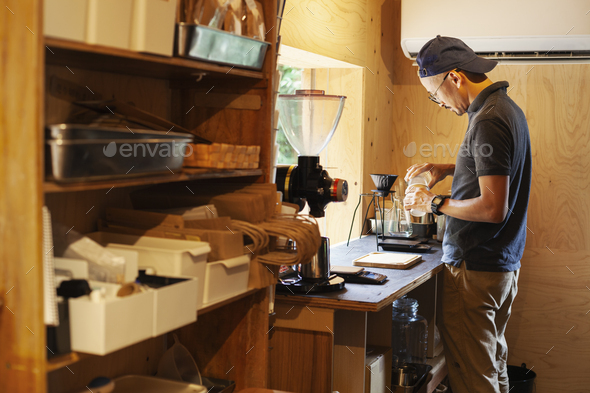 Japanese man wearing baseball cap and glasses standing in an Eco Cafe, preparing cup of coffee. - Stock Photo - Images