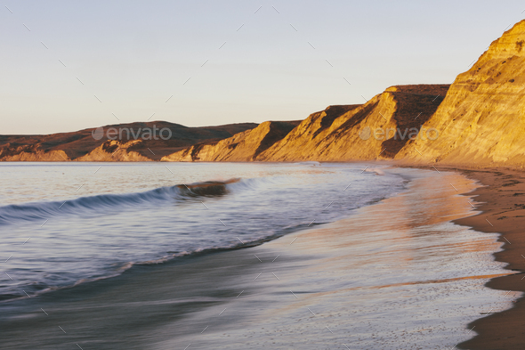 Steep cliffs and beach with surf at dawn - Stock Photo - Images