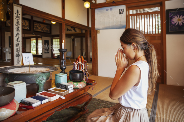 Two Japanese women kneeling in Buddhist temple, praying. - Stock Photo - Images
