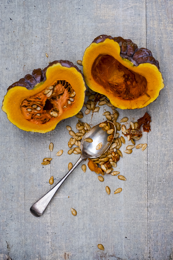 High angle close up of silver tablespoon and purple pumpkin with orange flesh cut in half. - Stock Photo - Images