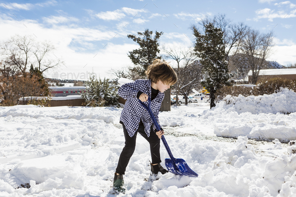 A six year old boy shoveling snow in driveway - Stock Photo - Images