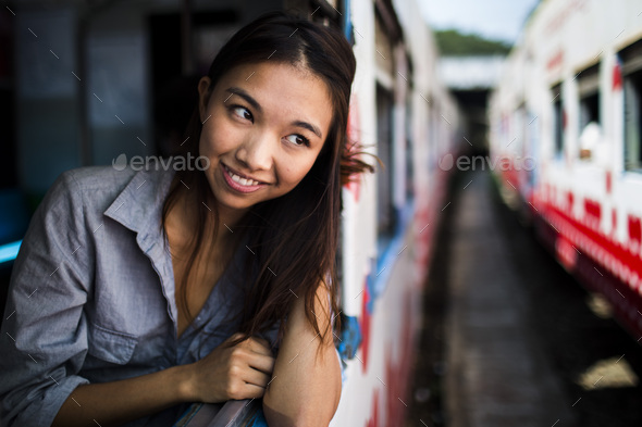Smiling young woman riding on a train, looking out of window. - Stock Photo - Images