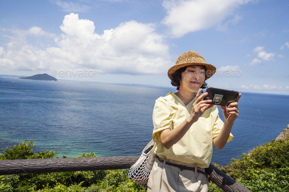 Japanese woman wearing hat standing on a cliff, taking selfie with mobile phone, ocean in the - Stock Photo - Images