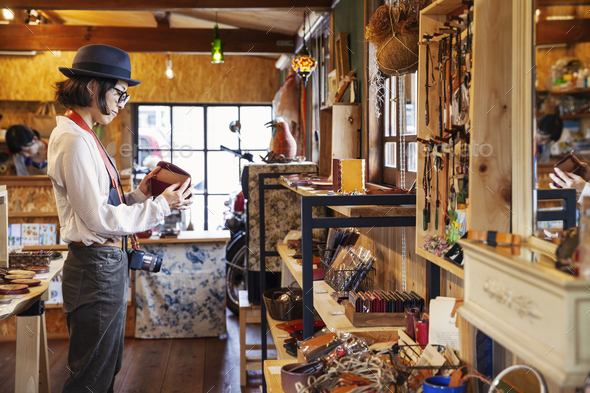 Japanese woman wearing hat and glasses browsing merchandise in a leather shop. - Stock Photo - Images