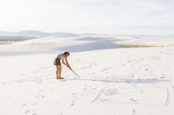 13 year old girl drawing in the sand, White Sands Nat'l Monument, NM - Stock Photo - Images