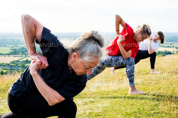 Group of women taking part in a yoga class on a hillside. - Stock Photo - Images