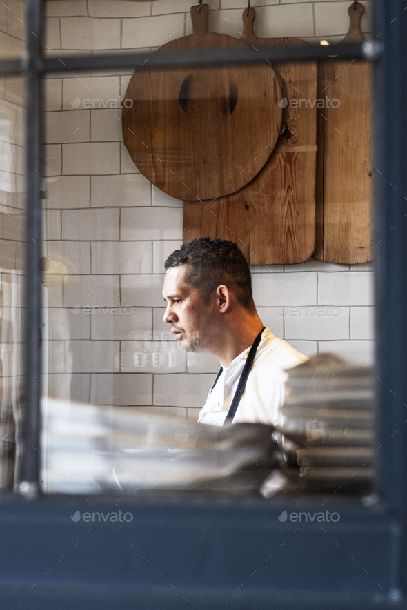 Portrait of male chef standing in a kitchen. - Stock Photo - Images