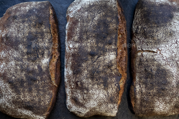 High angle close up of three freshly baked loaves of bread in an artisan bakery. - Stock Photo - Images