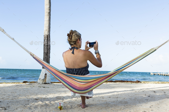 woman resting in hammock taking picture with smart phone, Grand Cayman Island - Stock Photo - Images