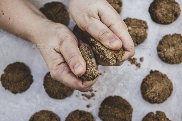 High angle close up of person breaking freshly baked chocolate cookie in half. - Stock Photo - Images