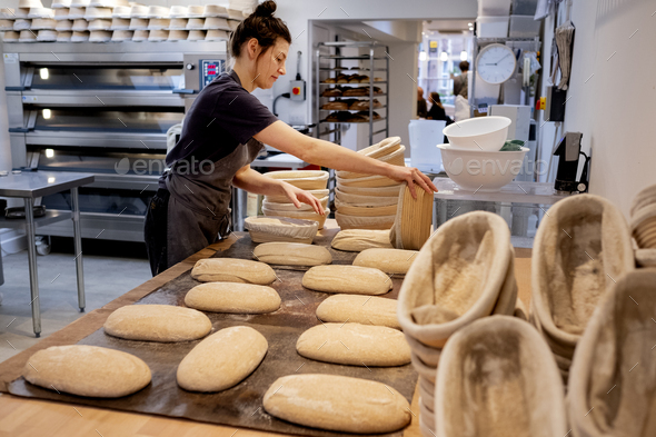 Woman wearing apron standing in an artisan bakery, shaping sourdough loaves for baking. - Stock Photo - Images