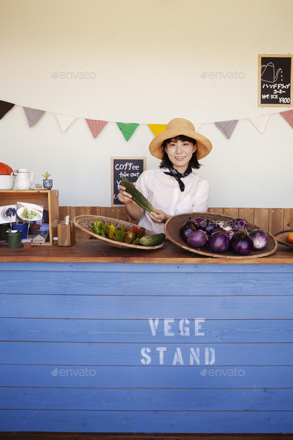 Japanese woman wearing hat standing behind counter in a farm shop, smiling at camera. - Stock Photo - Images