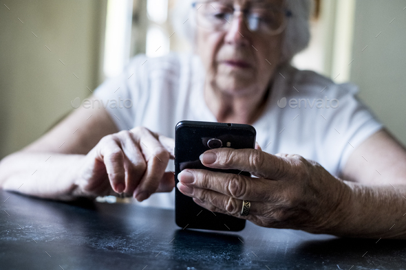 Close up of senior woman sitting at a table, using mobile phone. - Stock Photo - Images