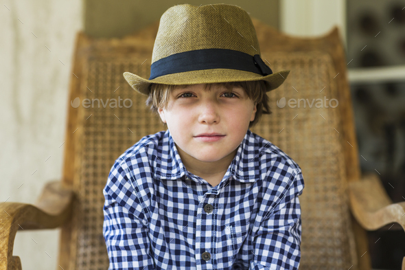 portrait of 6 year old boy sitting in wicker chair - Stock Photo - Images
