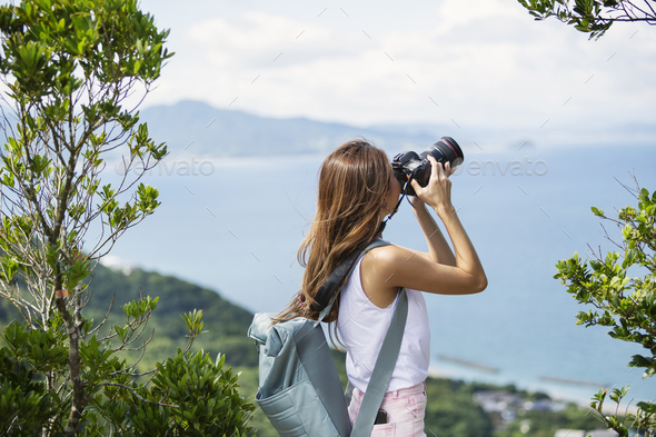 Japanese woman carrying backpack taking photograph on a cliff, ocean in the background. - Stock Photo - Images