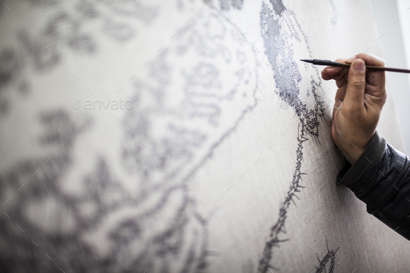 Close up of artist at work on a new painting in a studio. - Stock Photo - Images