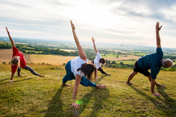 Group of women and men taking part in a yoga class on a hillside. - Stock Photo - Images
