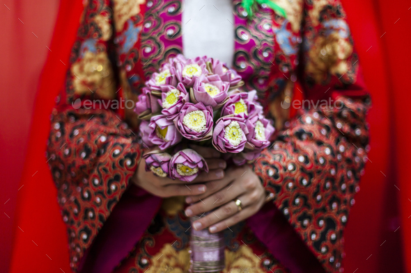 Close up of young Vietnamese bride wearing a colourful robe, holding a bouquet of lotus flowers. - Stock Photo - Images