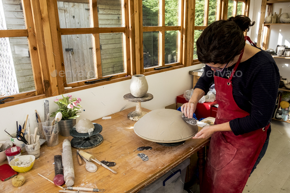 Woman wearing red apron standing in her ceramics workshop, working on clay bowl. - Stock Photo - Images