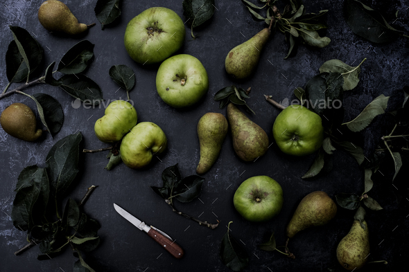 High angle close up of green pears and Bramley apples on black background. - Stock Photo - Images