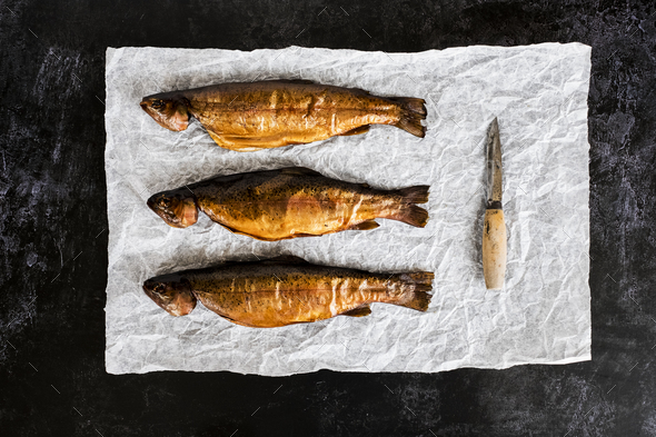 High angle close up of three freshly smoked whole trout and a knife on a white paper. - Stock Photo - Images