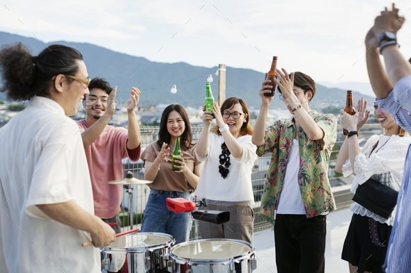 Smiling group of young Japanese men and women standing on a rooftop in an urban setting, drinking - Stock Photo - Images