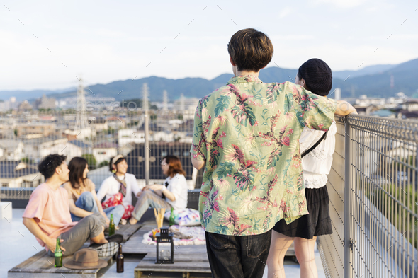 Group of young Japanese men and women on a rooftop in an urban setting. - Stock Photo - Images