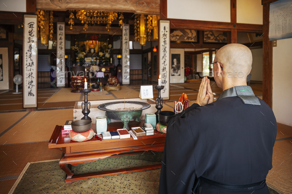 Buddhist priest kneeling in Buddhist temple, praying. - Stock Photo - Images