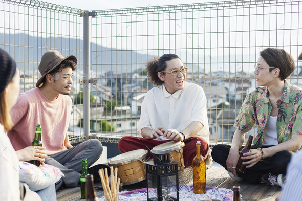 Group of young Japanese men and women sitting on a rooftop in an urban setting, drinking beer. - Stock Photo - Images