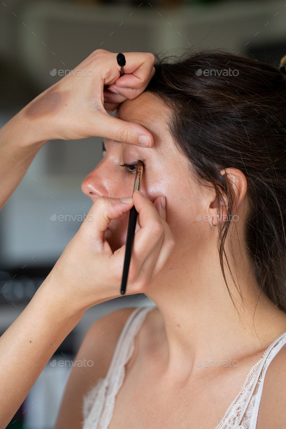 A professional make up artist at work, creating a look for a young woman. - Stock Photo - Images