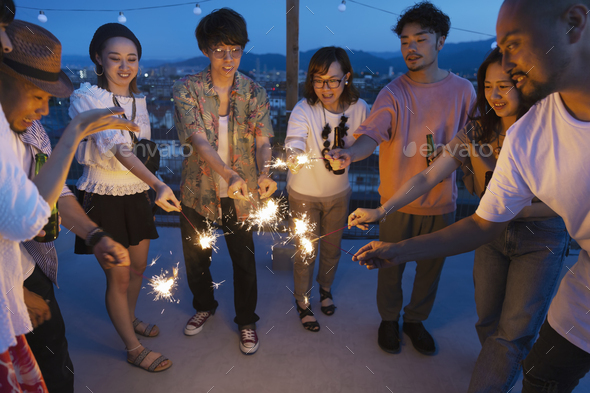 Group of young Japanese men and women with sparklers on a rooftop in an urban setting. - Stock Photo - Images