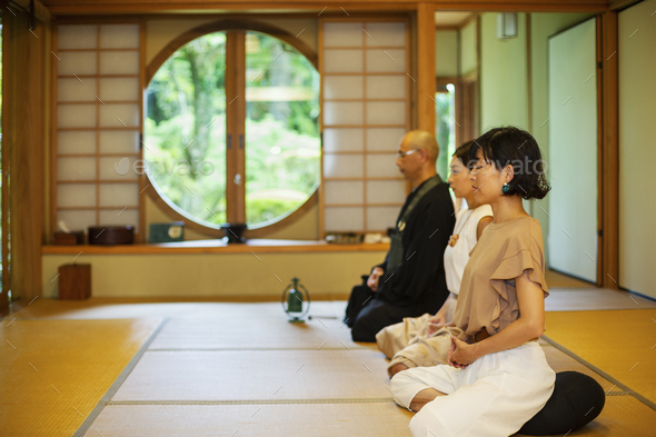 Two Japanese women and Buddhist priest kneeling in Buddhist temple, praying. - Stock Photo - Images