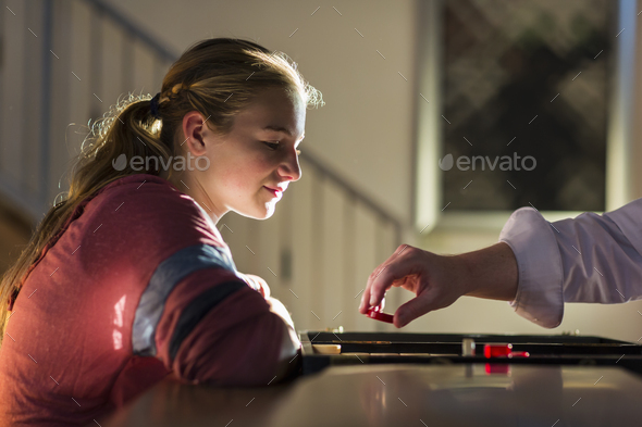 profile of 13 year old girl at sunset playing board game - Stock Photo - Images