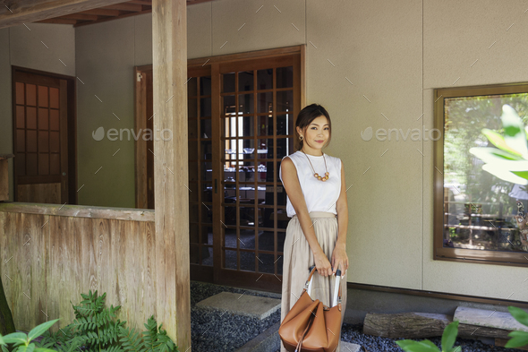 Japanese woman standing on a porch, holding handbag. - Stock Photo - Images