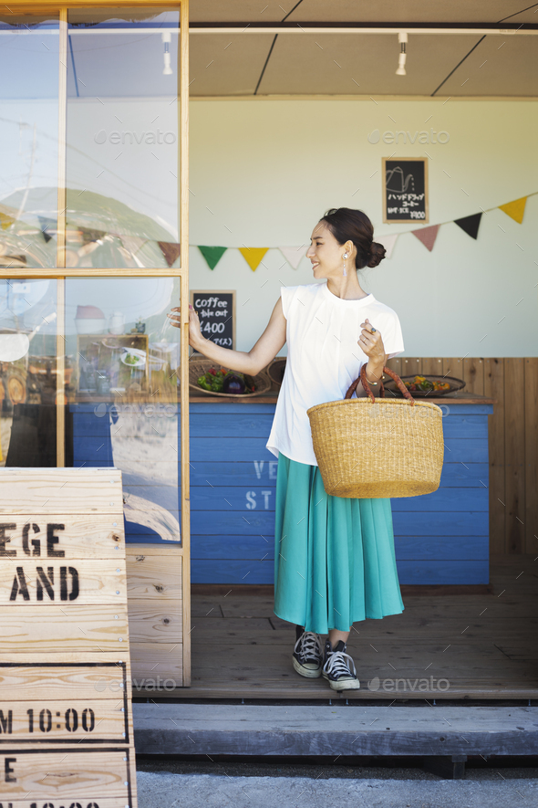 Japanese woman standing outside a farm shop, holding shopping bag. - Stock Photo - Images