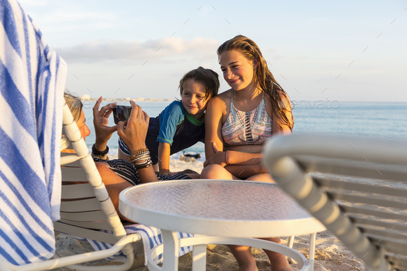 mother and her children enjoying the beach at sunset, Grand Cayman Island - Stock Photo - Images