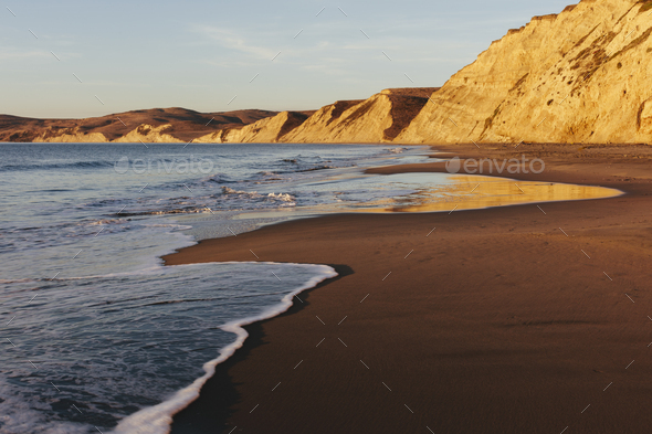 Beach at dawn, with sheer cliffs and rocks. - Stock Photo - Images