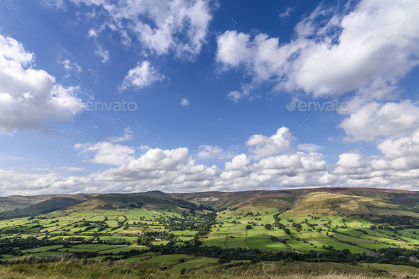 Landscape with fields and distant mountains under a cloudy sky, Peak District National Park. - Stock Photo - Images