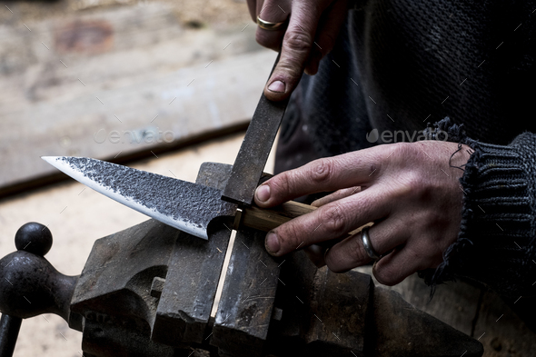 High angle close up of person working on handmade knife using a file. - Stock Photo - Images