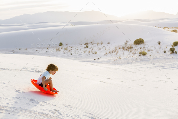 6 year old boy sledding down dunes, White Sands Nat'l Monument, NM - Stock Photo - Images