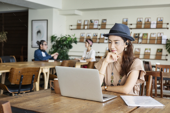 Group of young Japanese professionals working on laptop computers in a co-working space. - Stock Photo - Images
