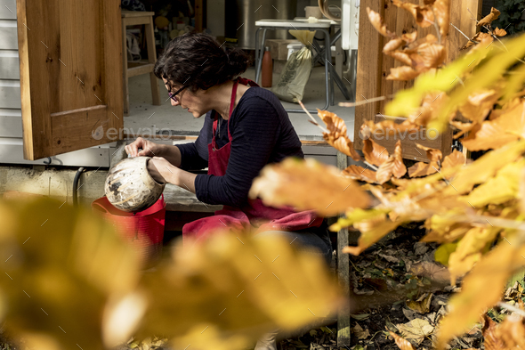 Woman wearing red apron sitting outside her ceramics workshop, holding vase. - Stock Photo - Images