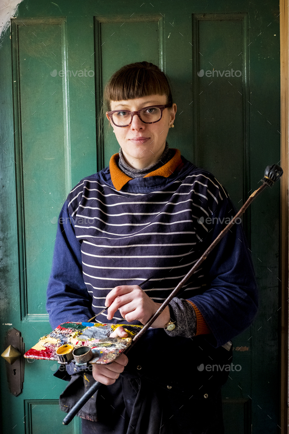Woman artist wearing glasses holding paintbrush, palette and Mahlstick, looking at camera. - Stock Photo - Images
