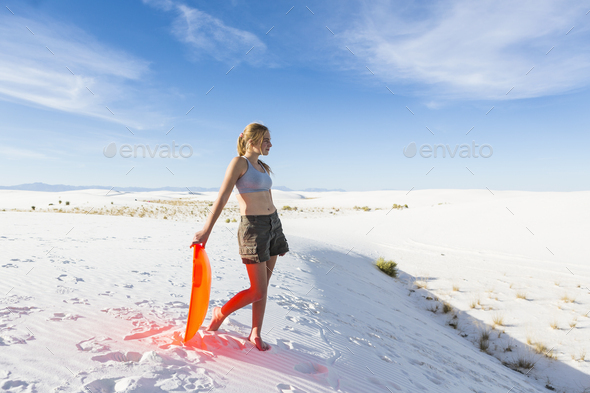 Teenage girl with a sledge at the top of a rise at White Sands Nat'l Monument, NM - Stock Photo - Images