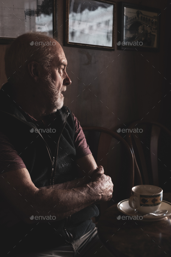 Bearded man sitting at a table with cup of coffee in a cafe. - Stock Photo - Images