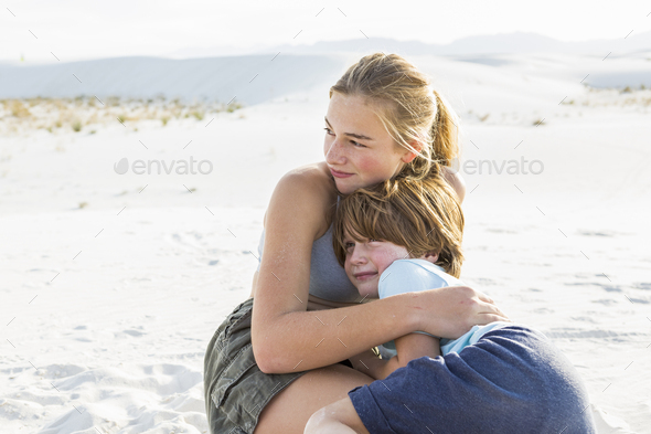 teen girl embracing her brother, White Sands Nat'l Monument, NM - Stock Photo - Images