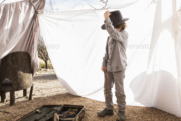 6 year old boy playing in an outdoor tent made of sheets - Stock Photo - Images