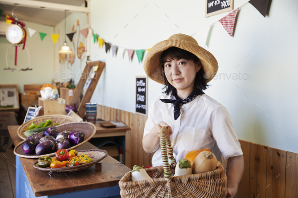 Japanese woman wearing hat working in a farm shop, smiling at camera. - Stock Photo - Images