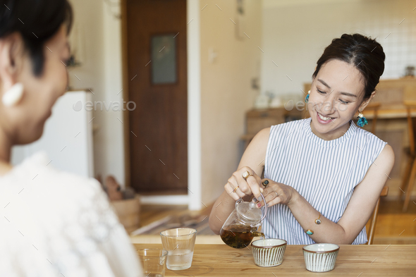 Two Japanese women sitting at a table in a vegetarian cafe, pouring tea. - Stock Photo - Images